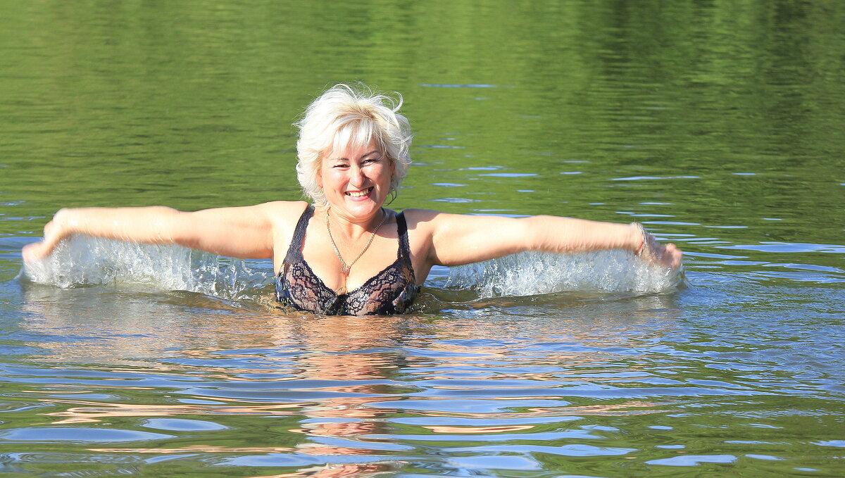 Женщина купается в реке, Солнце замирает вдалеке, Нежно положив на плечи ей Руки золотых своих лучей - Марина Валиуллина