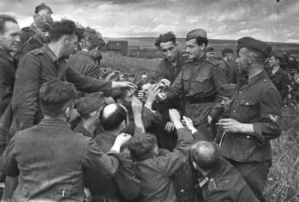 Советский солдат дает закурить немецким пленным. 1943 год.